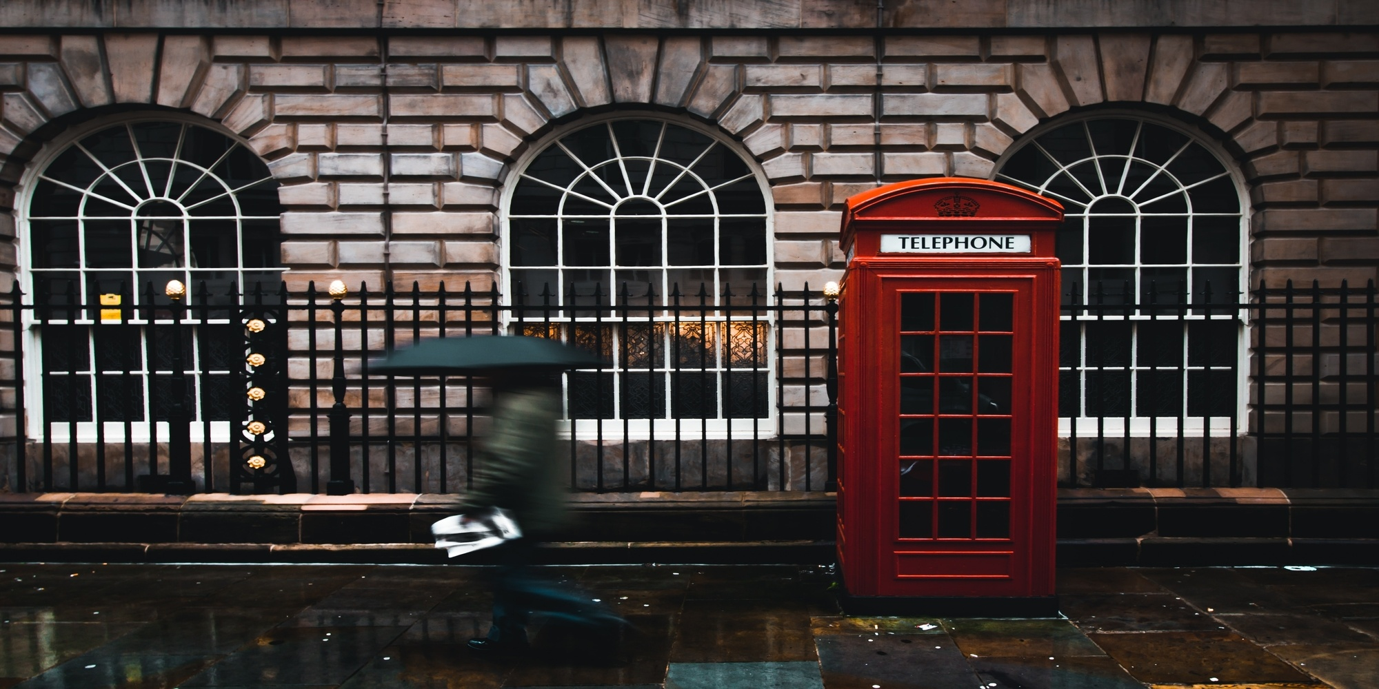 street in london with phone box and person walking