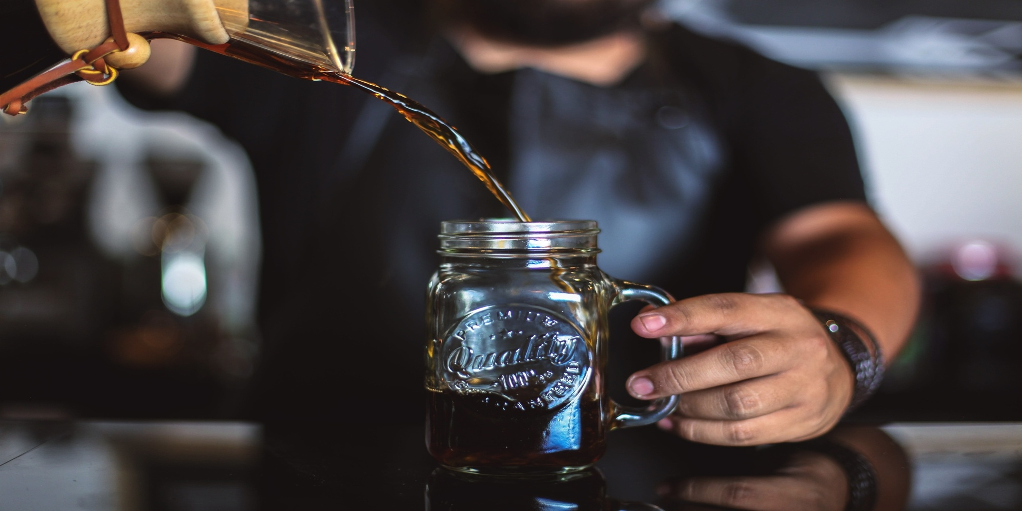 Man pouring specialty cold brew coffee into jar