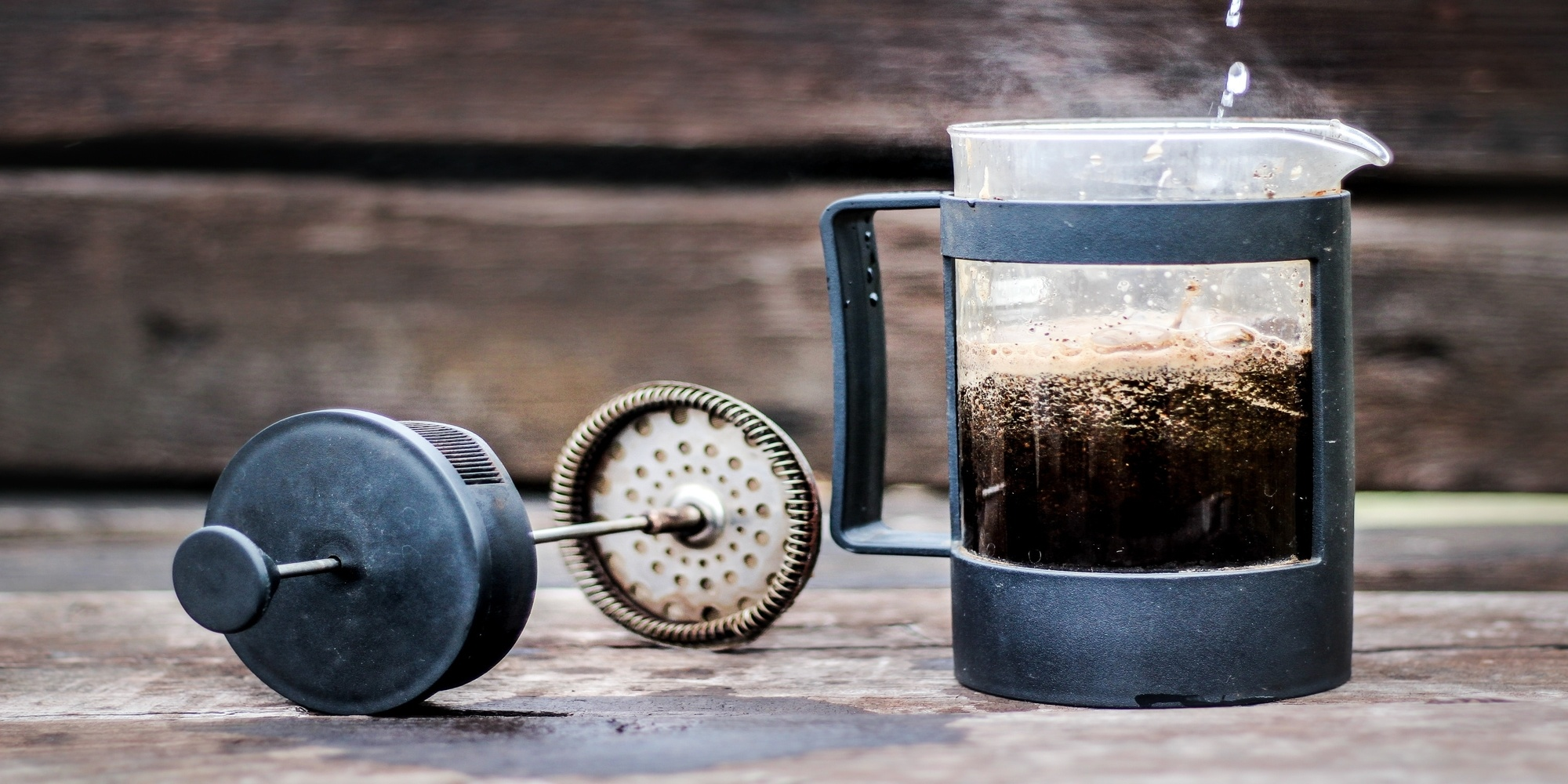french press pouring water into coffee