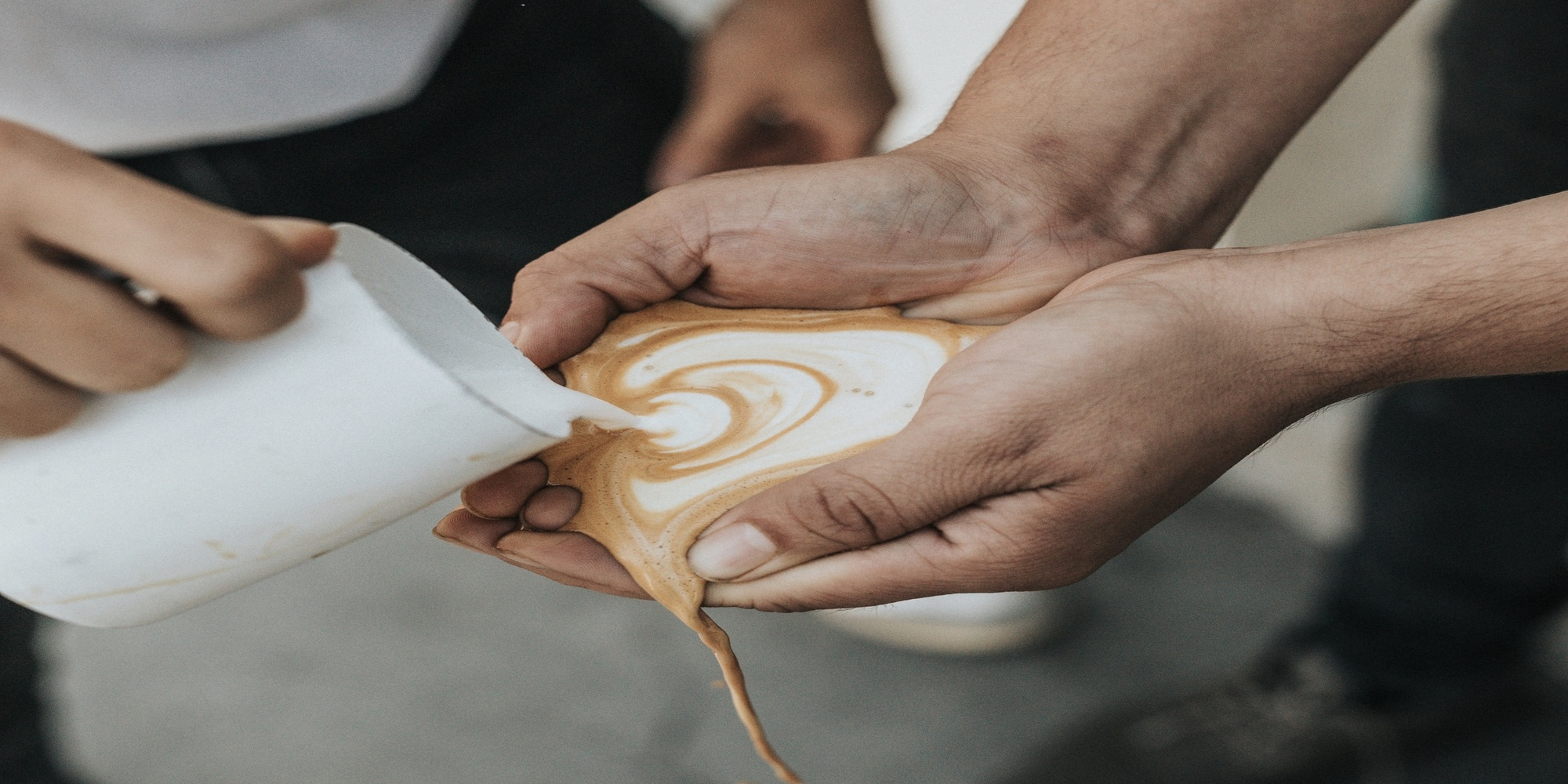 man pouring coffee into hands