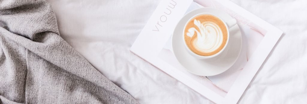 coffee sitting on white magazine in a bed
