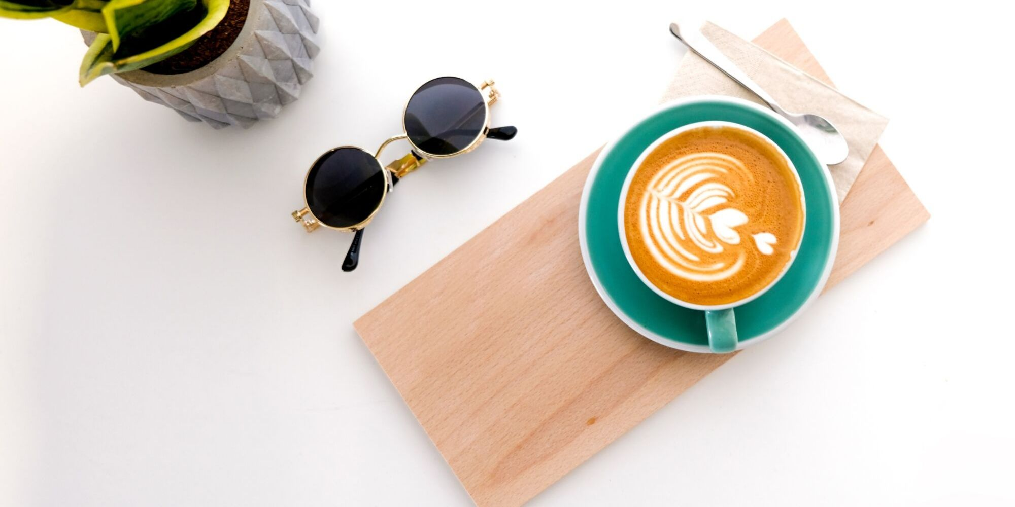 Specialty flat white coffee on table with plant