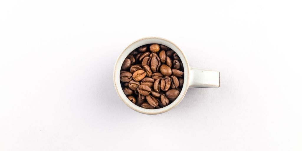 Small espresso mug filled with roasted coffee beans