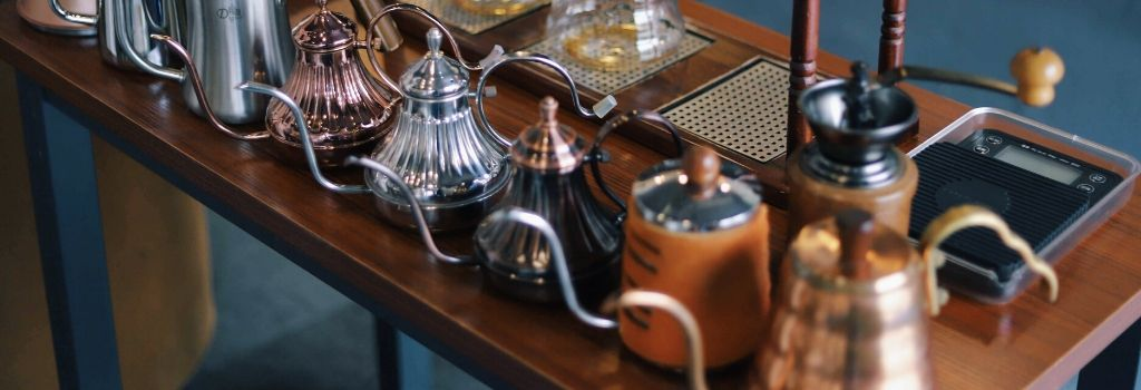 variety of different gooseneck kettles lined up on table