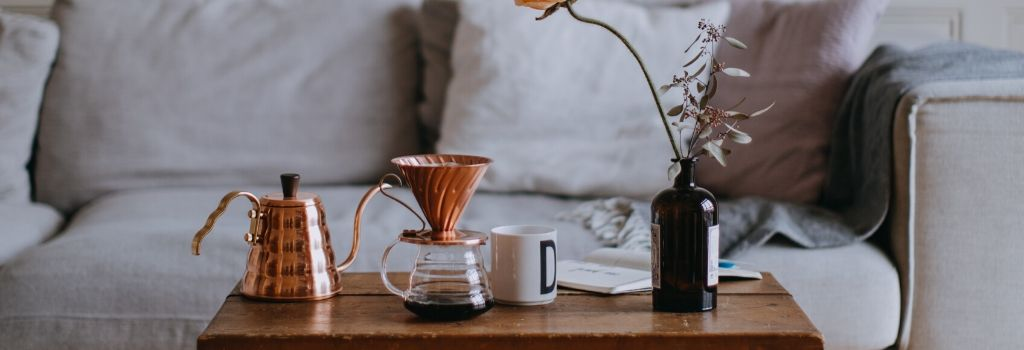 copper gooseneck kettle with v60 sitting on coffee table