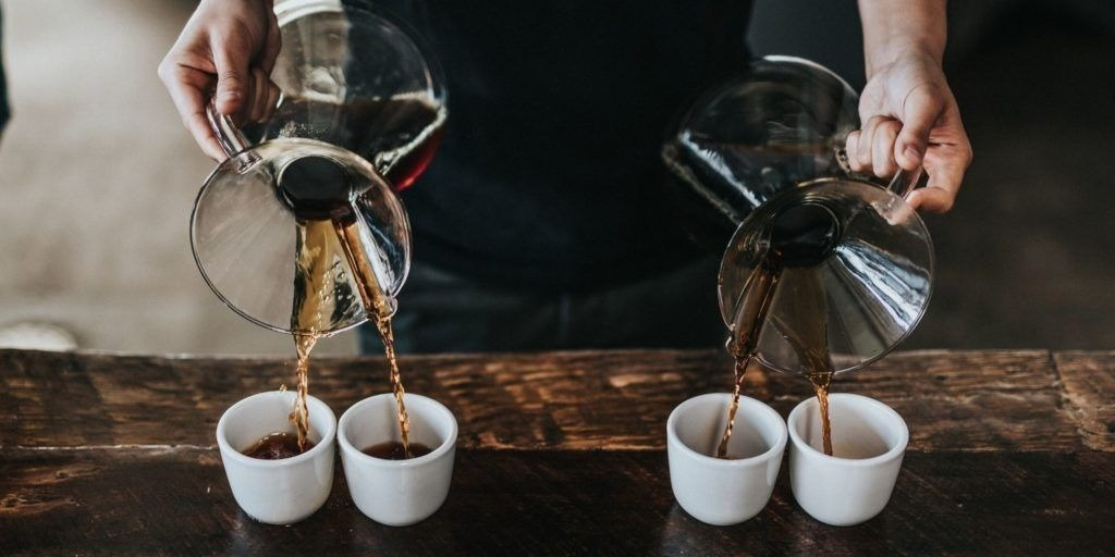 person pouring coffee from two chemex into cups