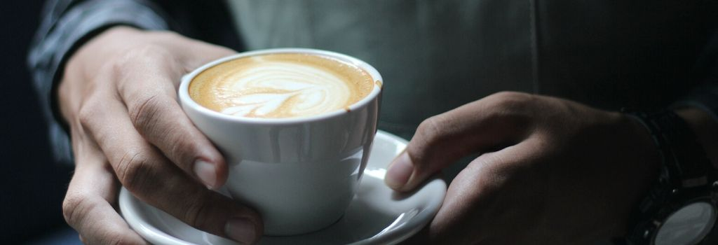 person holding coffee with heart milk design
