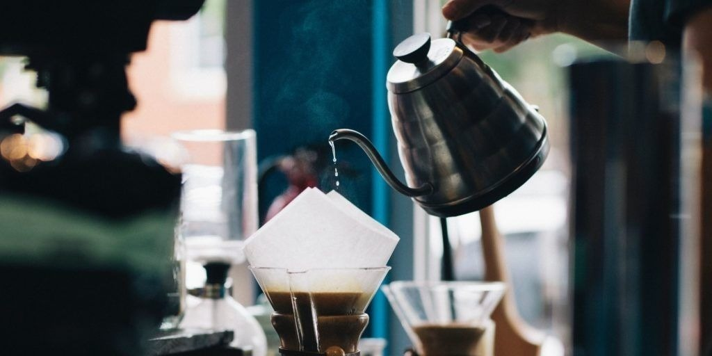Person pouring water into Chemex from gooseneck kettle