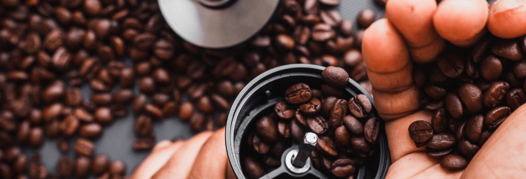 putting roasted coffee beans into coffee grinder