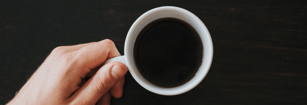 holding strong black coffee in white mug