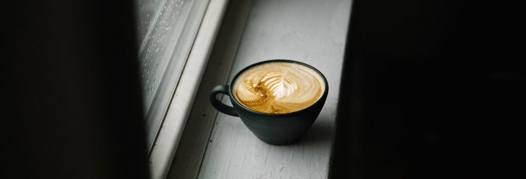 a brewed flat white coffee sitting on the window sill