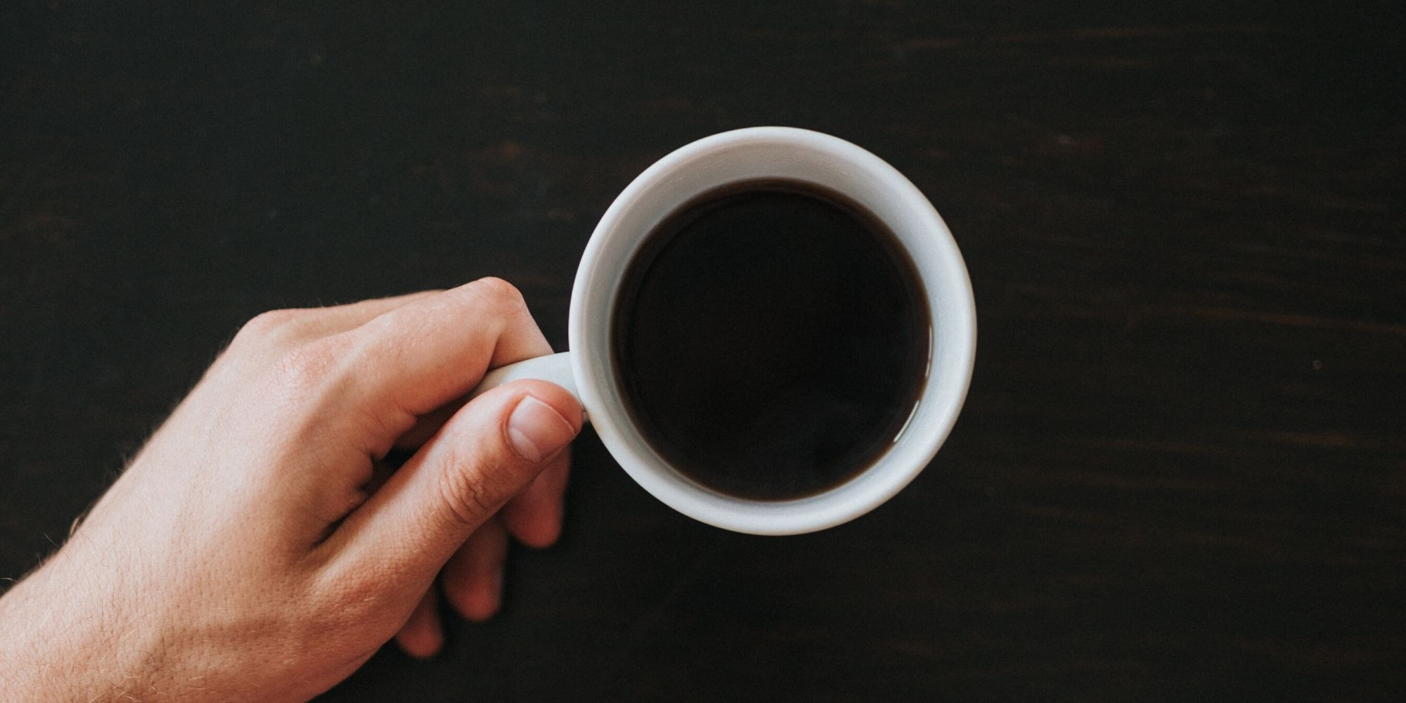 person holding black coffee in white cup