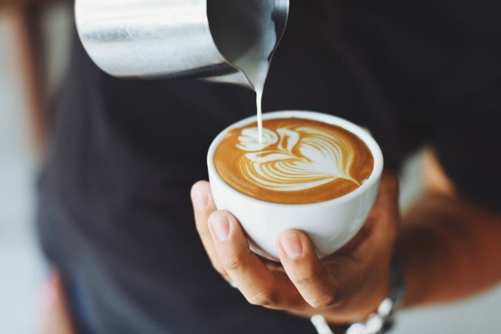 Man holding coffee cup pouring in milk