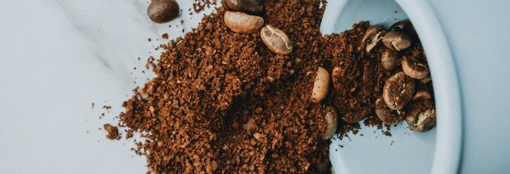 ground coffee beans spilling out of cup